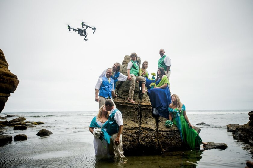 With a drone hovering, Ce and Steve Conner (kissing) and their wedding party pose for photos at Sunset Cliffs.