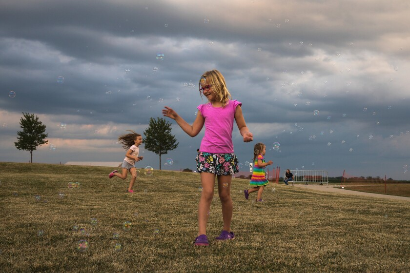 Luca Giltner, 5, from left, Krista Giltner, 8, and Calla Giltner, 2, play with bubbles at Chill on the Hill, a weekly summer concert series in Mt. Zion, Ill., on June 29, 2017.