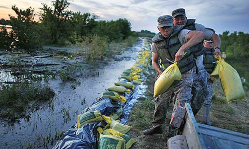 Army National Guard members load sandbags into an ATV as they fight to keep a levee near the flooding Mississippi River from washing out. Many Midwestern towns could not afford the amount the Army Corps of Engineers would have required them to chip in for flood-protection projects.