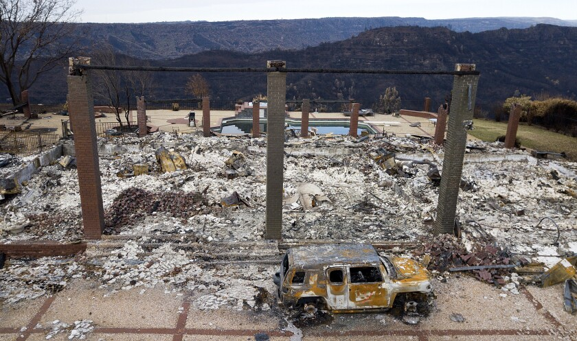 FILE - In this Dec. 3, 2018, file photo, a vehicle rests in front of a home leveled by the Camp Fire in Paradise, Calif. Homeowners and renters in 22 northern California counties are guaranteed not to lose their property insurance policies over the next year after the state announced a moratorium on Monday, Sept. 20, 2021, for people who live near recent wildfires. Insurance Commissioner Ricardo Lara issued a temporary moratorium for about 325,000 policyholders who live near those wildfires. (AP Photo/Noah Berger, File)