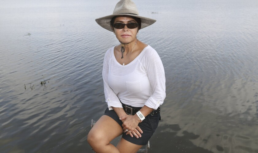 Olivia López sits on the dock at her waterfront home on Lake Corpus Christi on July 24 in Lake City, Texas. López says she'll forever be traumatized after working at a family detention center.