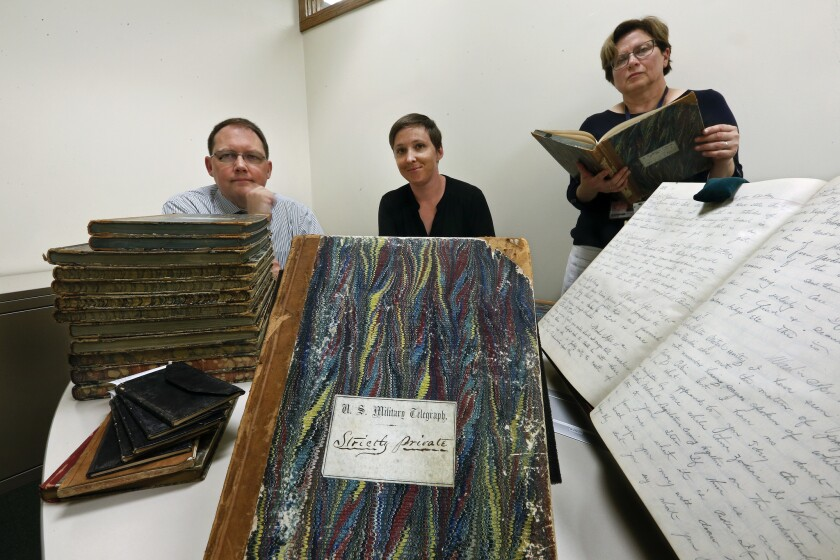 Digital project librarian Mario M. Einaudi, left, library assistant Kate Peck and curator Olga Tsapina photographed with the ledgers containing Civil War telegrams from Abraham Lincoln, his Cabinet and members of the Union Army.