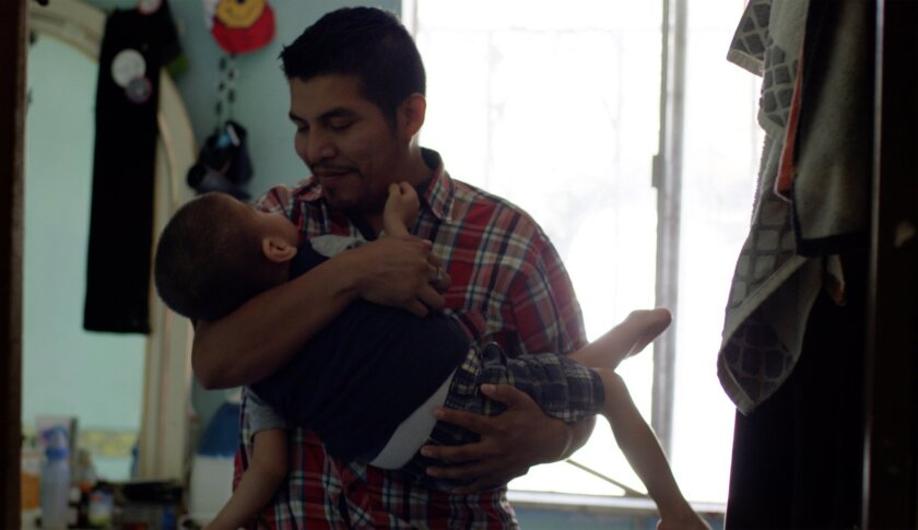 Heriberto Francisco-Mateo cradles his 11-year-old son, Jesus. Both Jesus and his brother, Alan, suff