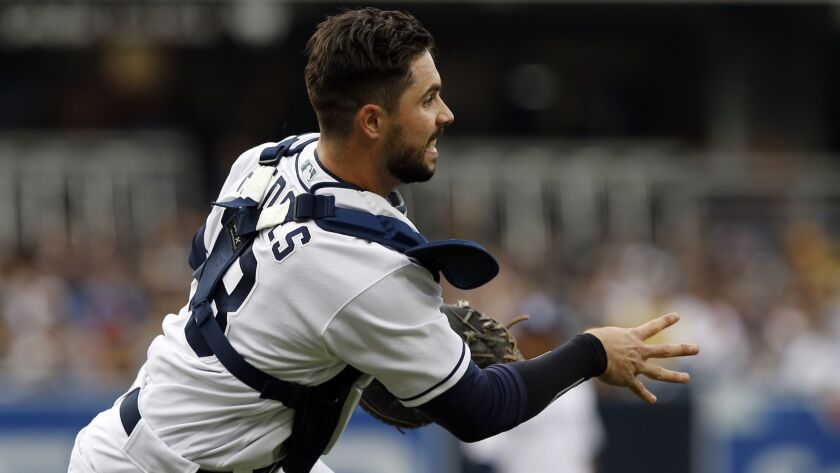 Padres catcher Austin Hedges throws out a Milwaukee Brewers runner at first base on Saturday.