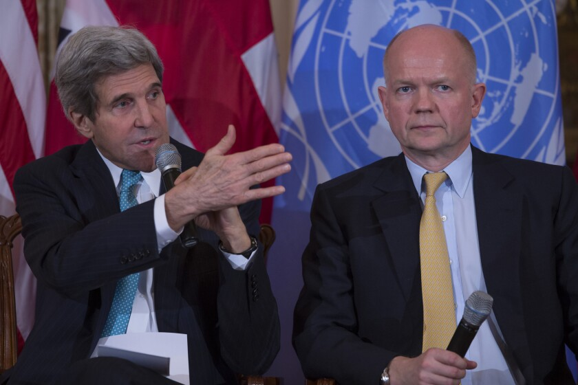 British Foreign Secretary William Hague listens at right as U.S. Secretary of State John F. Kerry speaks.