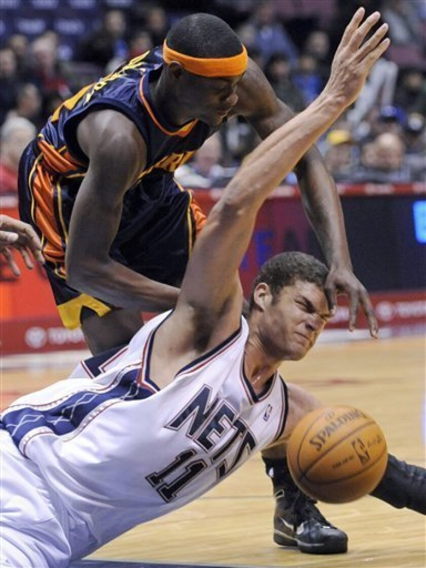 New Jersey Nets' Brook Lopez (11) dives after a loose ball in front of Golden State Warriors' Anthony Morrow during the first quarter of an NBA basketball game Wednesday, Dec. 9, 2009 in East Rutherford, N.J. (AP Photo/Bill Kostroun)