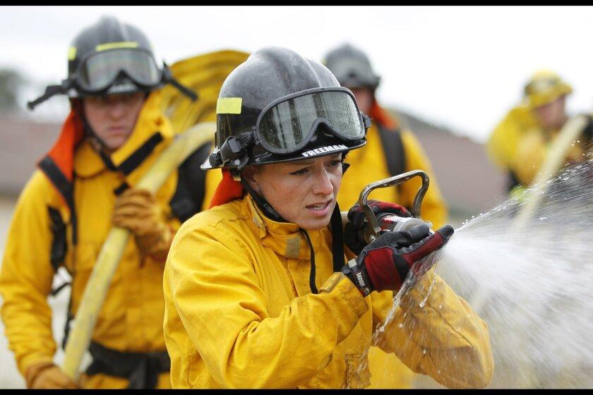 Palomar Fire Academy cadet Siene Freeman sprays water.