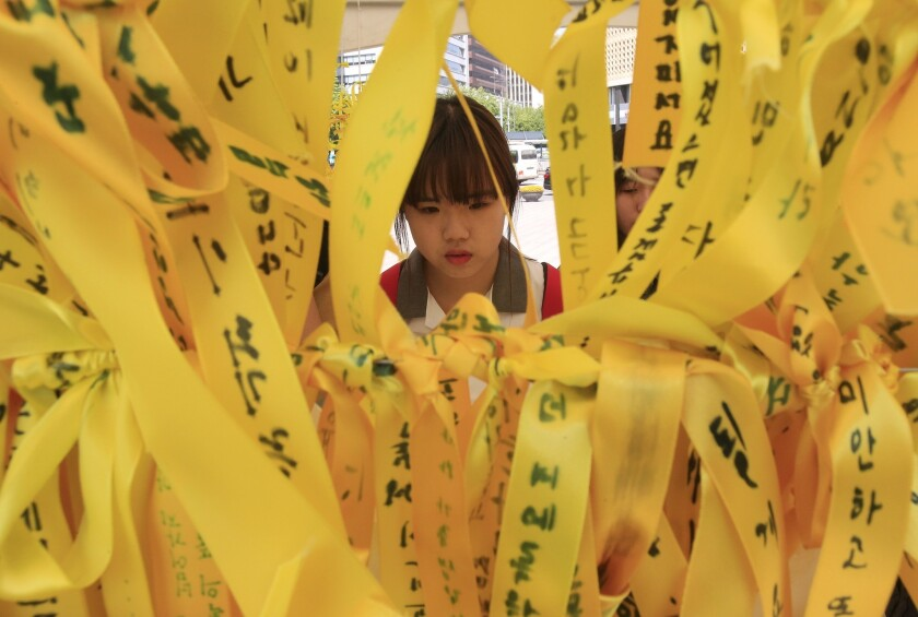 A high school student reads messages written on ribbons for victims of the sunken ferry Sewol at a memorial altar in Seoul.