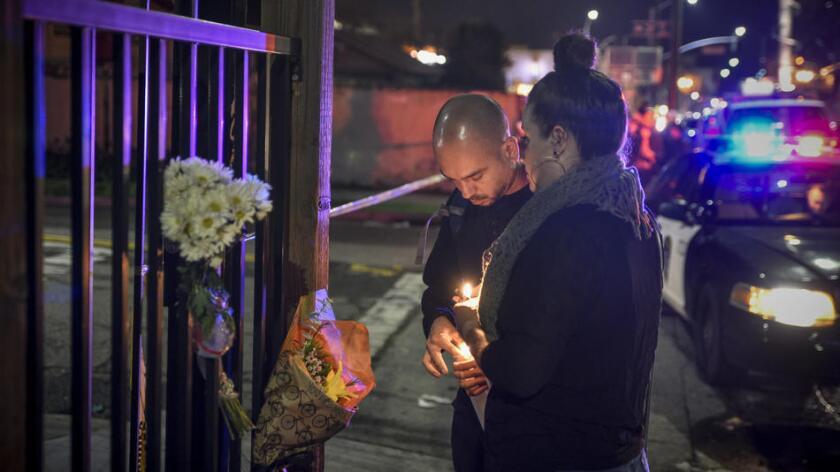 Dino Graniello (i) y Jessie Xenakis encienden veladoras cerca de la escena donde se incendió la bodega, en Oakland. David Butow/Redux/For the Los Angeles Times