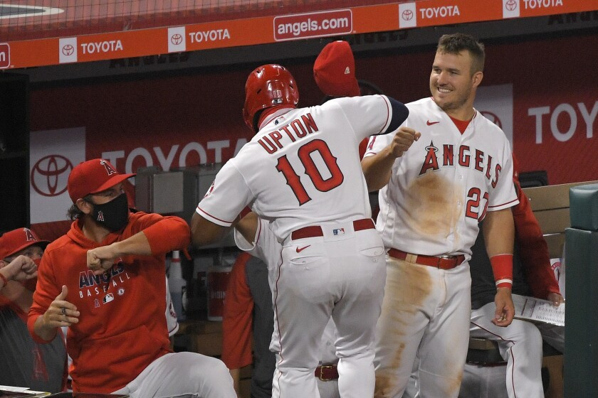 Los Angeles Angels' Justin Upton, center, is congratulated by teammates, including Mike Trout, right, after hitting a solo home run during the sixth inning of a baseball game against the Seattle Mariners Wednesday, July 29, 2020, in Anaheim, Calif. (AP Photo/Mark J. Terrill)