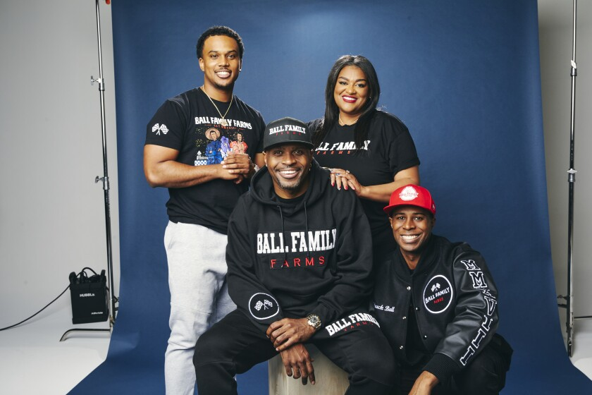 Four people wearing Ball Fall Farms merchandise posing for a photo