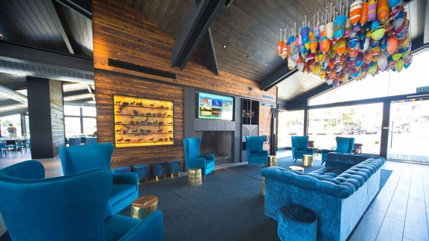The wood-fire bar at Decoy Dockside Dining in San Marcos is decorated with a ceiling installation of fishing buoys and and tin animal cutouts from an antique shooting gallery.