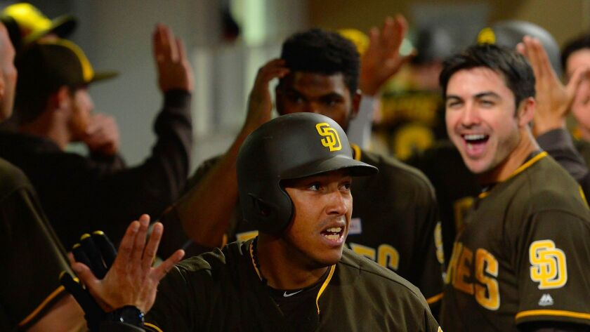 San Diego Padres second baseman Yangervis Solarte (center) is congratulated after hitting a two-run home run during the fifth inning against the Colorado Rockies as left fielder Chase d'Arnaud (right) reacts at Petco Park.