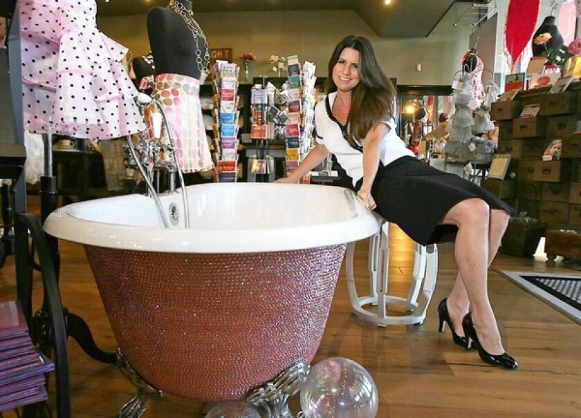Lori Gardner with one of her specialized tubs covered in crystals at Fleur De Lys in Costa Mesa.
