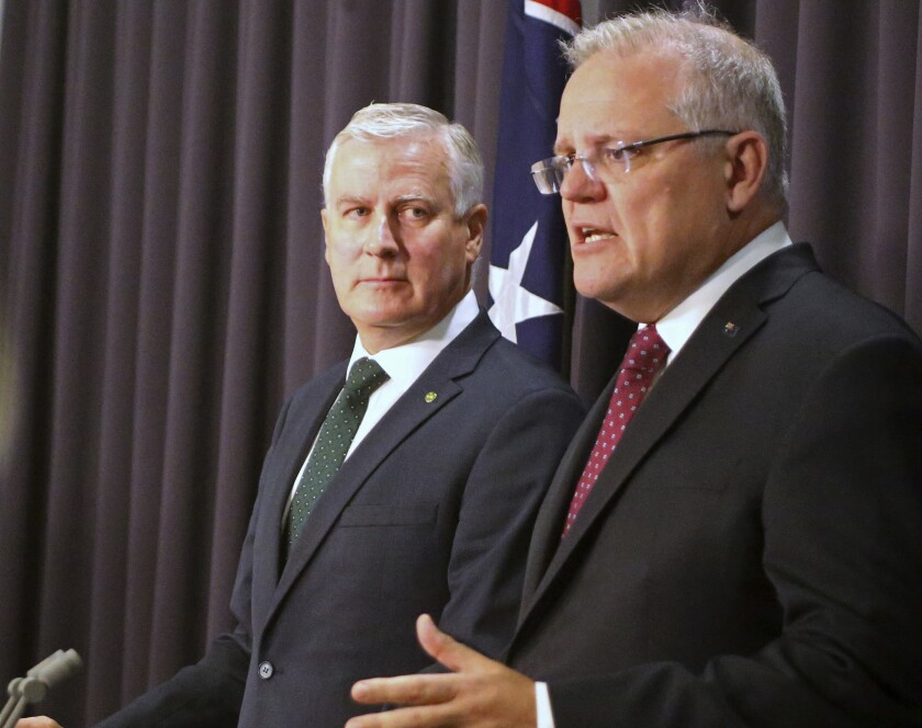 Australian Prime Minister Scott Morrison, right, and Deputy Prime Minister Michael McCormack brief the media in Canberra, Thursday, Feb. 6, 2020. Morrison announced changes to his Cabinet after two ministers resigned this week following political turmoil. (AP Photo/Rod McGuirk)