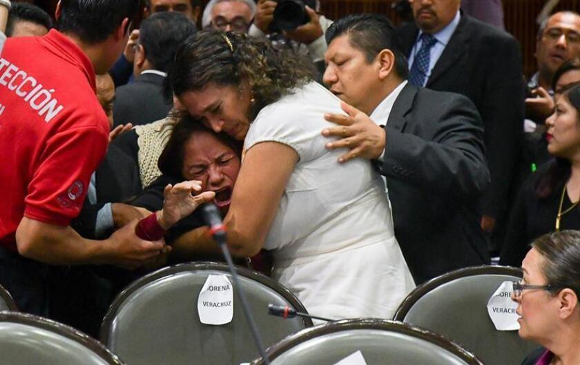 Legisladores reconfortan a la diputada Carmen Medel Palma, del Movimiento Regeneración Nacional (Morena), luego de que recibiera la noticia de que su hija había sido asesinada. EFE/STR