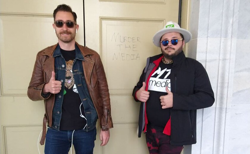 "Nicholas Ochs and Nicholas DeCarlo stand in front of a door with the words ""Murder the media."""
