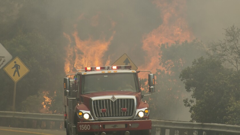 Firetrucks make their way past flames from the Wragg fire near Putah Creek off Highway 128 west of Winters on Wednesday.