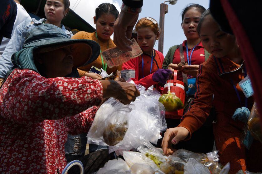 Cambodian workers buy food outside their factory in Phnom Penh.