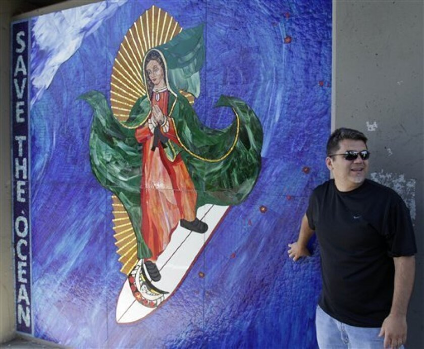 FILE - In this May 27, 2011 file photo, Nick Dinapoli, of San Diego, stands in front of the Surfing Madonna mosaic under a train bridge in Encinitas, Calif. The San Diego County beach city of Encinitas on Tuesday June 21, 2011 said that Mark Patterson, the artist who created the popular but illegal mosaic, will pay a $500 fine and all costs of relocating it from public property. (AP Photo/Gregory Bull, File)