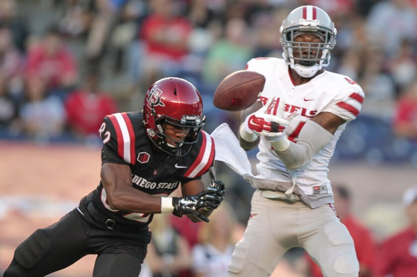 A pass to the Aztecs' Lloyd Mills, left, is broken up by UNLV's Kenny Keys during the second quarter at Qualcomm Stadium in San Diego on Saturday. An interference call was made.