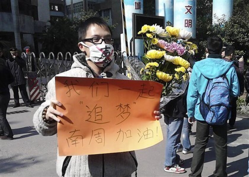 "In this photo taken and provided by activist Wu Wei, a man wearing a mask with words ""Silent"" holds a banner reading: ""Let's chase our dreams together, go Southern Weekly newspaper"" during a protest outside the headquarters of the newspaper in Guangzhou, Guangdong province Monday, Jan. 7, 2013. A dispute over censorship at the Chinese newspaper known for edgy reporting has prompted a few hundred people to gather in a rare street protest urging Communist Party leaders to allow greater political freedom. (AP Photo/Wu Wei) EDITORIAL USE ONLY"