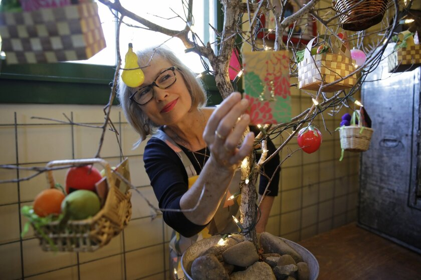 """In this photo taken Tuesday, Oct. 20, 2015, Carrie Brown, author of """"The New Christmas Tree,"""" adjusts an ornament on The Giving Tree that is featured in her book at the Jimtown Store in Healdsburg, Calif. Brown is the owner of the Alexander Valley country store that dates to 1893. (AP Photo/Eric Ri"""