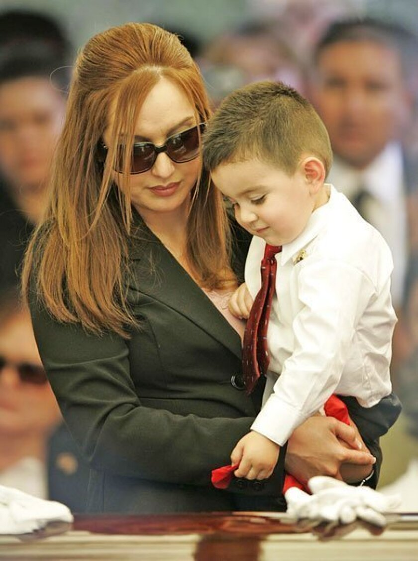 Rosalie Rosas, widow of slain Border Patrol Agent Robert Rosas, held son Robert Matthew, 2, as he set a rose petal on his father's casket at a service yesterday in El Centro.  (John Gibbins / Union-Tribune)
