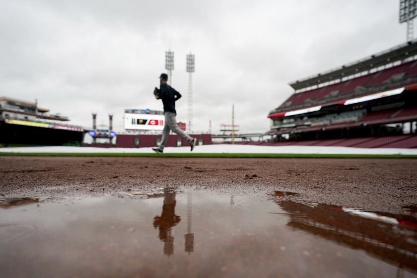 Pittsburgh Pirates' starting pitcher Chad Kuhl (39) runs past the tarp covered field prior to a baseball game against the Cincinnati Reds in Cincinnati, Wednesday, Sept 22, 2021. (AP Photo/Bryan Woolston)