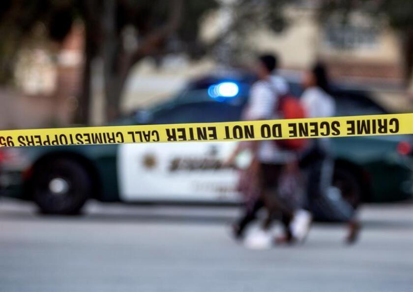 Un grupo de personas camina frente al lugar donde un anciano mató a su esposa en Florida. EFE/Archivo