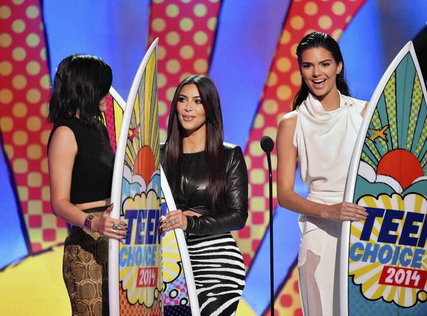 TV personalities Kylie Jenner, left, Kim Kardashian, center, and Kendall Jenner appear onstage during Fox's 2014 Teen Choice Awards at the Shrine Auditorium in L.A.