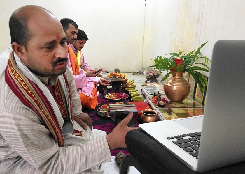 Priest Narayan Shastri, left, conducts a puja service via Skype for the Shubhpuja company in Noida, India. In Hinduism, there are elaborate pujas for virtually every life event.