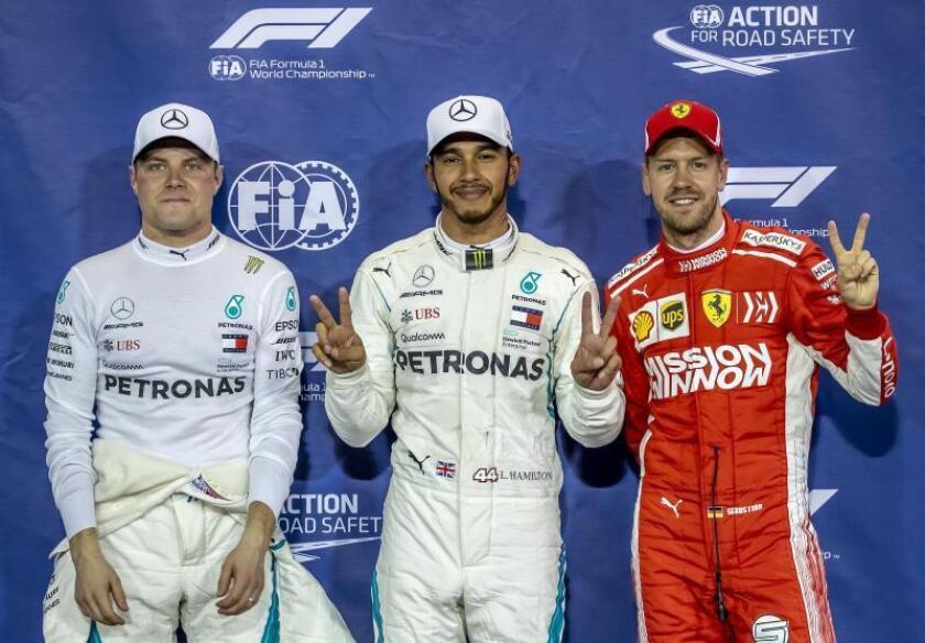 El piloto británico de Fórmula Uno Lewis Hamilton (c), del equipo Mercedes AMG GP, junto a Valtteri Bottas (i), también del Mercedes AMG GP y el alemán Sebastian Vettel (d), de la escudería Ferrari en el Circuito Yas Marina Abu Dabi. EFE/EPA