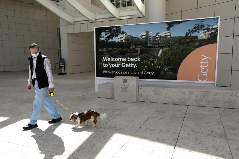 A man walking his dog wears a mask outside the Getty Center in Los Angeles.