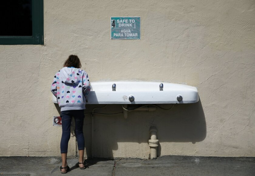 In this Sept. 16, 2015 photo, a student drinks from a water fountain below a sign signaling the water as safe to drink at Westport Elementary School in Ceres, Calif. The school, which draws on its own wells for its drinking fountains, sinks and cafeteria, is one of about 10 water systems in the far