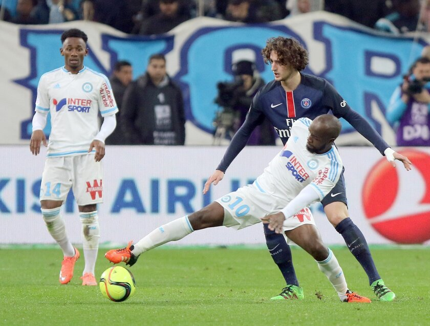 Marseille's Lassana Diarra, front,  challenges for the ball with Paris Saint Germain's Adrien Rabiot, during the League One soccer match between Marseille and Paris Saint-Germain, at the Velodrome Stadium, in Marseille, southern France, Sunday, Feb. 7, 2016. (AP Photo/Claude Paris)