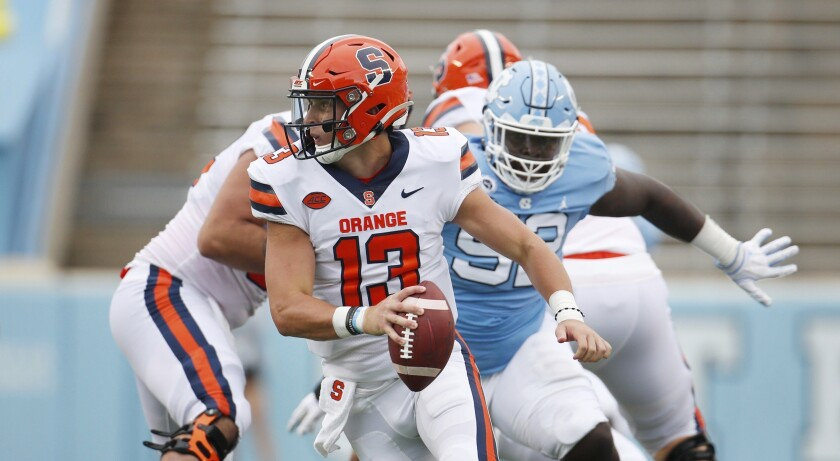 FILE - Syracuse quarterback Tommy DeVito (13) scrambles to avoid North Carolina defender Jahlil Taylor (52) in first half of an NCAA college football game in Chapel Hill, N.C., in this Saturday, Sept. 12, 2020, file photo. Syracuse success will depend on a defense that finished 112th overall in 2020, and an offense that struggled behind two-year starter Tommy DeVito, who missed much of last season with an injury.(Robert Willett/The News & Observer via AP, Pool, File)