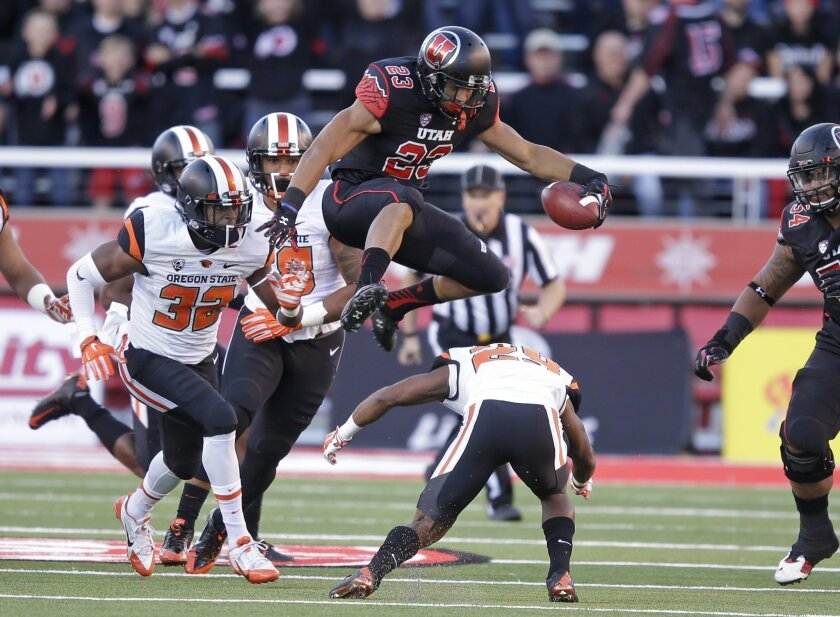 FILE - This Saturday, Oct. 31, 2015, file photo, shows Utah running back Devontae Booker (23) leaping over Oregon State cornerback Dwayne Williams (29) as teammate linebacker Jonathan Willis (32) pursues in the first quarter during an NCAA college football game  in Salt Lake City. Running backs Leo