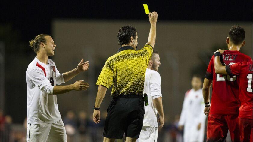 SDSU midfielder Casey Macias receives a yellow card after knocking down UNLV defender Adam Musovski.