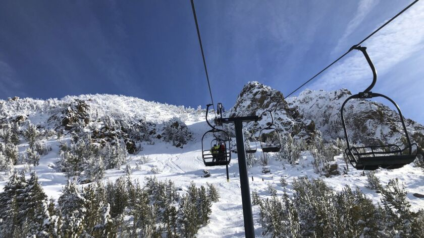 In this Friday, Dec. 7, 2018, skiers going up a lift at Mammoth Mountain ski resort in Mammoth Lakes