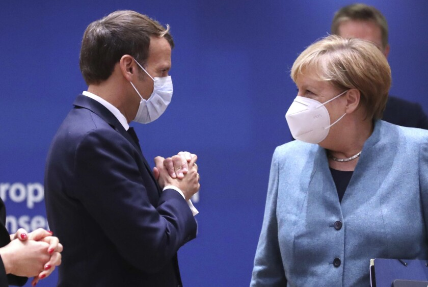 German Chancellor Angela Merkel, right, speaks with French President Emmanuel Macron arrives for a round table meeting at an EU summit at the European Council building in Brussels, Thursday, Oct. 15, 2020. European Union leaders are meeting in person for a two-day summit amid the worsening coronavirus pandemic to discuss topics ranging from Brexit to climate and relations with Africa. (Yves Herman, Pool via AP)