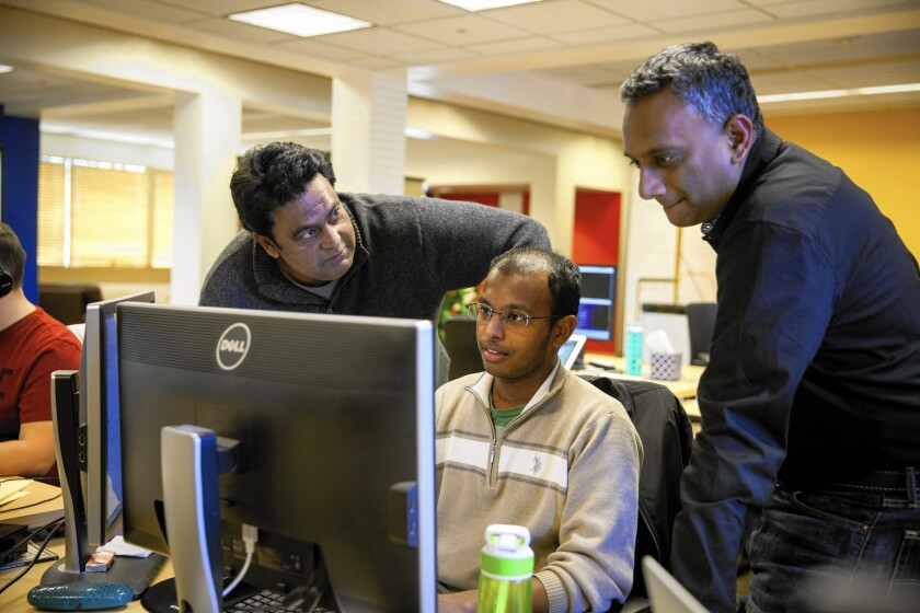 Urban Engines co-founder Balaji Prabhakar, left, and chief executive Shiva Shivakumar, right, discuss code changes with Deepak Merugu in Los Altos.
