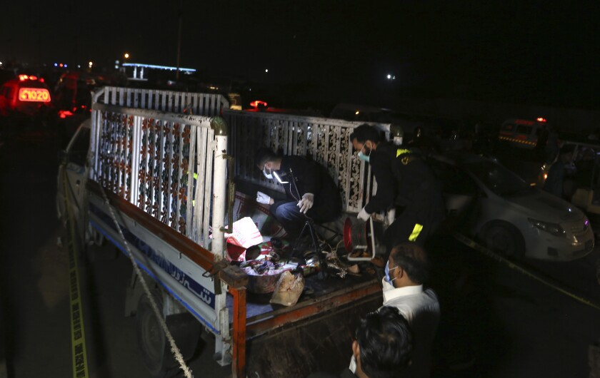 Pakistani investigators examine a truck at the site of an explosion, in Karachi, Pakistan, Saturday, Aug. 14, 2021. Attackers targeted a truck in the Pakistani port city of Karachi, killing multiple people and wounding others. An initial investigation suggests the attackers followed the truck and then threw hand grenades or some sort of improvised explosive devices at one side of the truck, police said. (AP Photo/Fareed Khan)