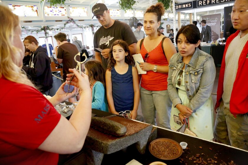 From left, Glen Gieger and his wife Rema Gieger watch with their daughters Briahna, 5, and McKenna, 7, as demonstrators with the Mars Chocolate History Ambassadors show the historical process of how chocolate used based on a recipe from the 1750's to be made into a drink. The demonstrations were held at the second annual Chocolate Festival held at the Maritime Museum of San Diego.