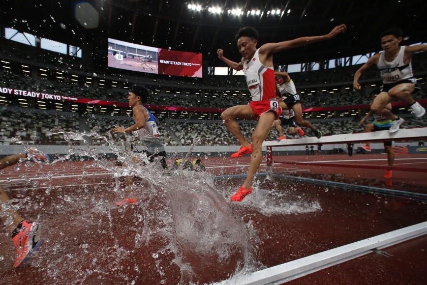 Atletas japoneses compiten en los 3.000 metros con obstáculos durante una competencia de ensayo por los Juegos Olímpicos de Tokio, el domingo 9 de mayo de 2021, en el Estadio Nacional de Tokio. (AP Foto/Shuji Kajiyama)