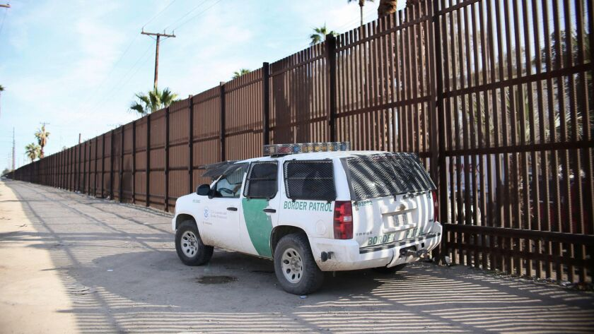 A Border Patrol agent looks over the U.S.-Mexico border wall in Calexico, Calif.