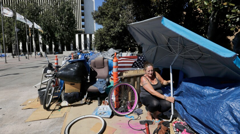Homeless for several months now, Marnie Alcaraz finds a little shade under an umbrella at her encampment in the shadow of the Orange County Courthouse.