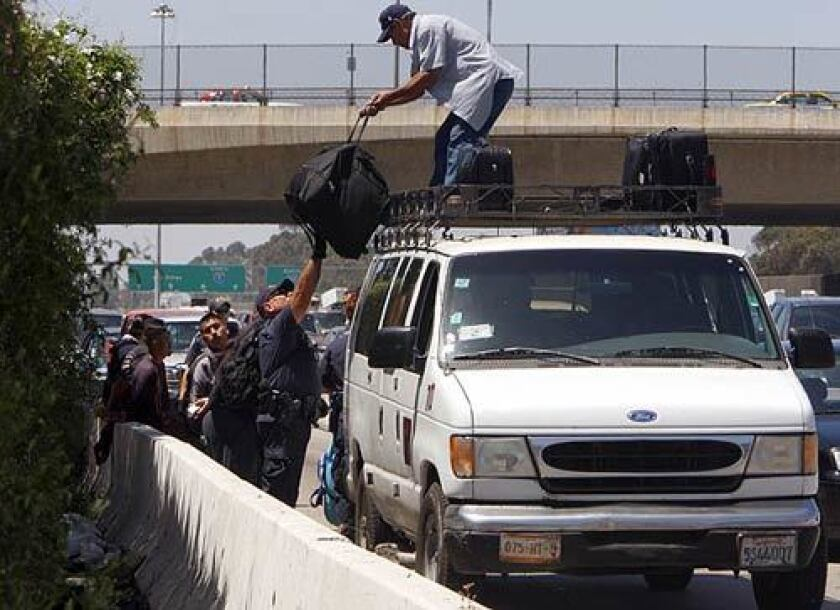 A van driver unloads luggage belonging to several passengers being detained by federal agents at the checkpoint just north of the border. The operations occur at random, unannounced times.