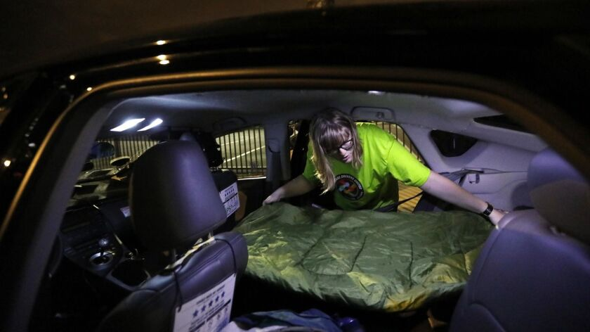 Jos Cashone, 28, lays out a sleeping bag in her car near Los Angeles International Airport. Cashone is studying computer science at Santa Monica College.