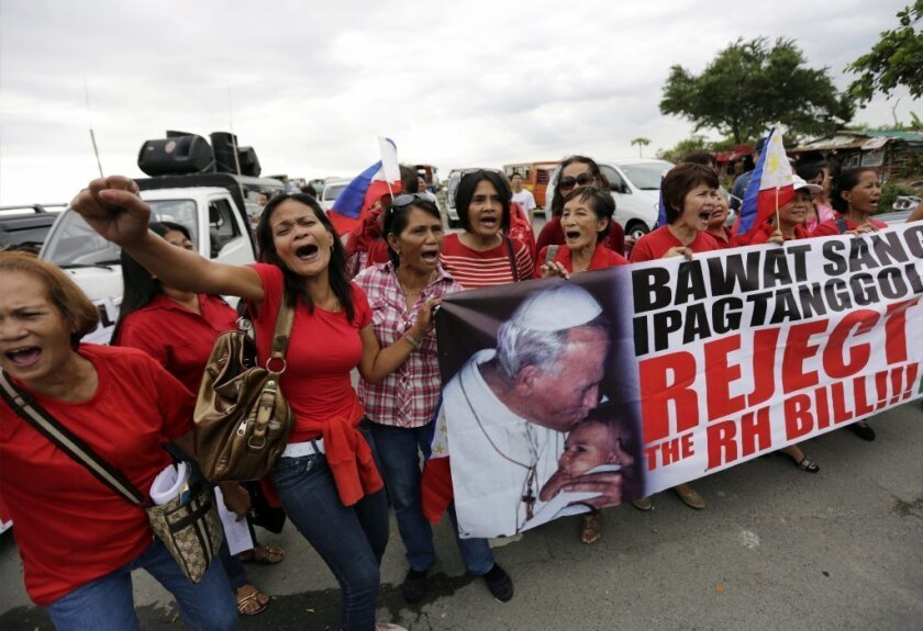 Filipino Catholics stage a demonstration against the passing of a reproductive health law in front of the Senate building on Monday.